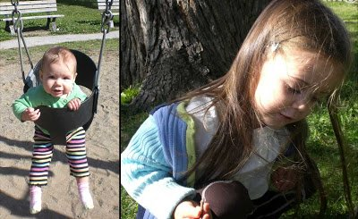 At the park, baby swinging, preschooler exploring in the grass.