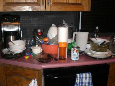 Untidy kitchen counter with stacks of dirty dishes.