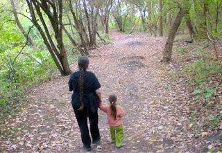 Mom and preschooler walking in the woods.