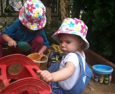 Girls playing in the sandbox.