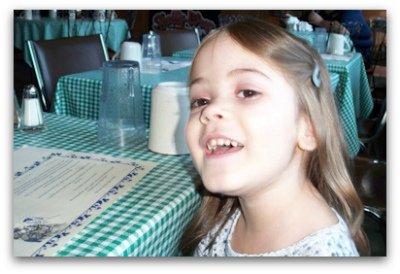 Happy preschooler eating breakfast at a restaurant.