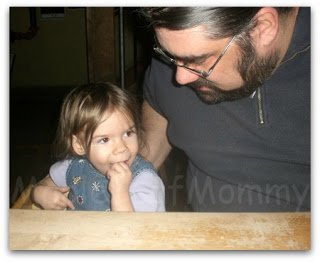 Happy toddler with her Dad eating at a restaurant.