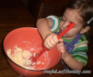 Preschooler helps mix margarine and sugar.