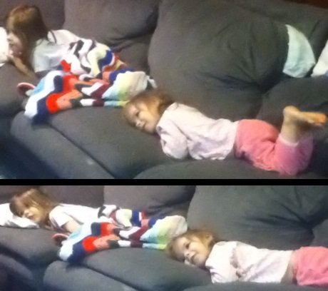 Toddler and preschooler sisters snuggling down for TV time together.