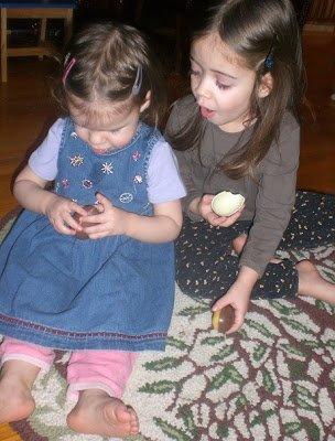 Two preschooler sisters enjoying Kinder Surprise eggs.