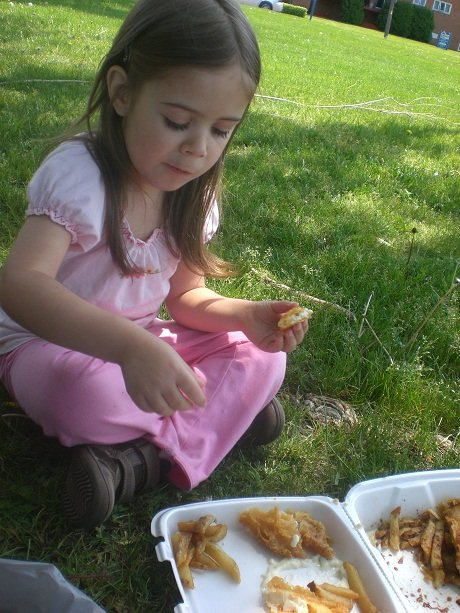Preschooler eating fish and chips at the park.