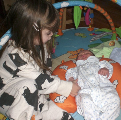Big sister with newborn baby sister.