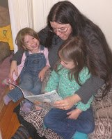 Mom reading with two young girls.
