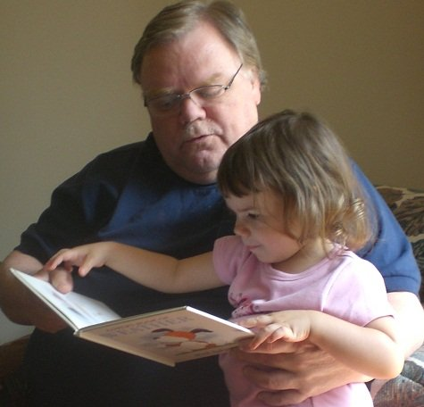 Her grandfather reads to my little girl.