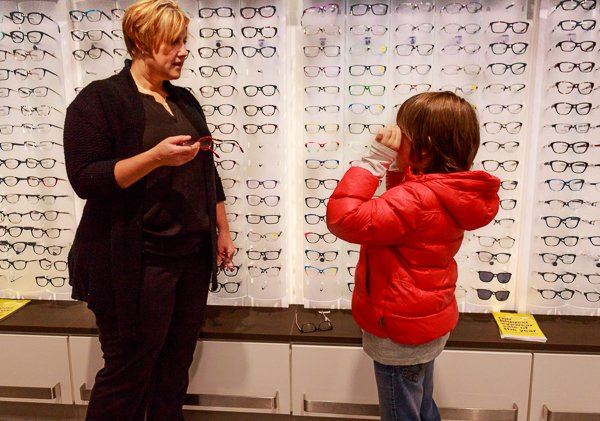 Super Centre Optical's optician on site, helping hcild choose free glasses.