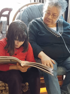 Grandmother reading with granddaughter.